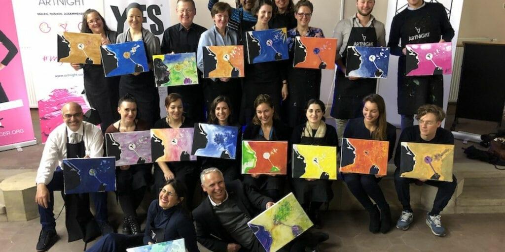 Gruppenbild mit Menschen und ihren gemalten Bildern
